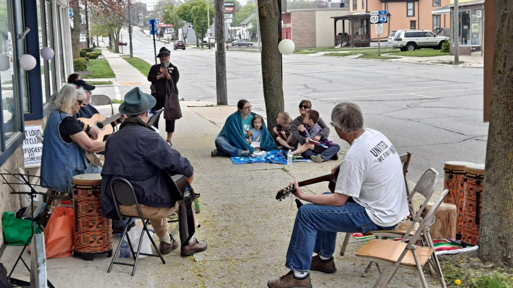 Music and families on the sidewalk at the People's Power Summit Tamale Sale.